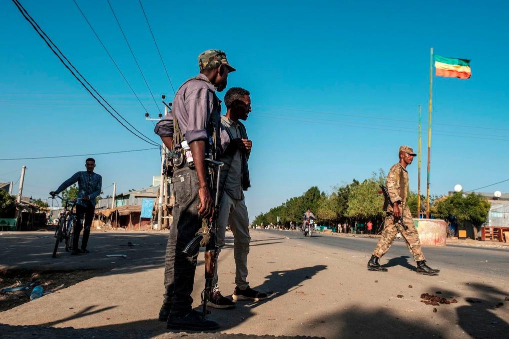 I membri della milizia Amhara si trovano in una strada mentre un soldato cammina davanti a una bandiera imperiale etiope, a Mai Kadra, in Etiopia, il 21 novembre 2020